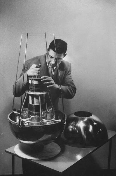 Iowa State University professor George H. Ludwig placing a tape recorder in a model of an American satellite - May 1957