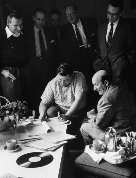 TV entertainer, Jackie Gleason, sitting at coffee table, signing new contract with CBS while manager and executives watch - 1956
