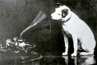 "Nipper the dog from painter Mark Henry Barraud's iconic image ""His Master's Voice"".  The phonograph is an Edison Bell cylinder phonograph"